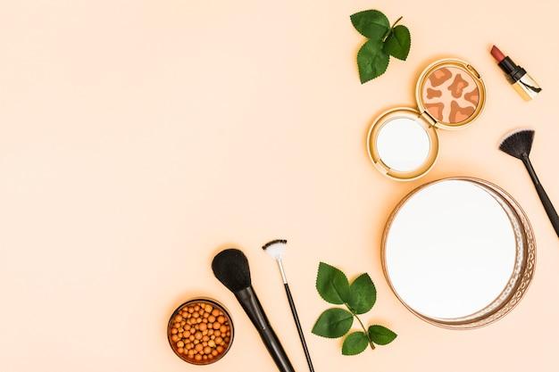 Espejo; bola de polvo de la cara; polvo compacto con pintalabios y pinceles de maquillaje. Foto gratis