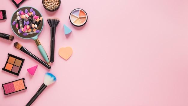 Espejo con sombras de ojos y pinceles en polvo sobre mesa rosa. Foto Premium