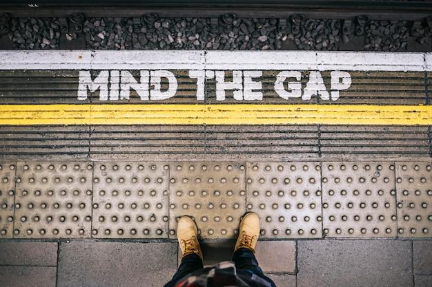 Esperando el metro en la estación desde la plataforma viendo las cartas de mind the gap Foto Premium