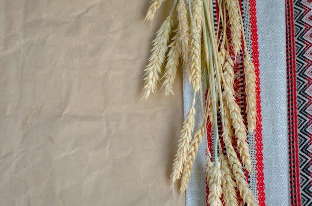 Espiguillas de centeno maduras de tela bordada popular y papel marrón de paquete de envoltura Foto Premium