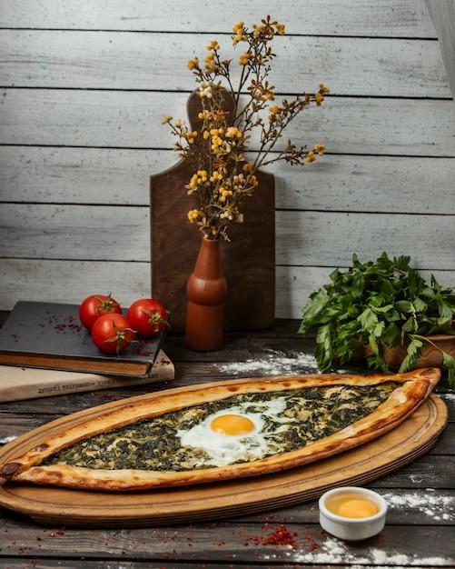 Espinaca pide con huevo sobre tabla de madera Foto gratis