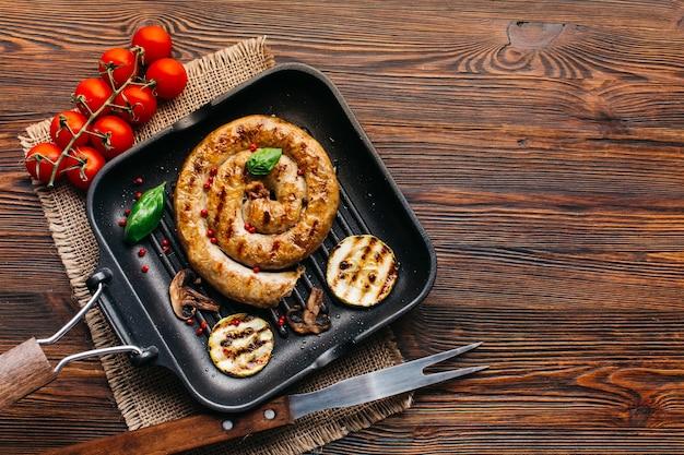 Espirales deliciosas salchichas a la parrilla con verduras rebanada en sartén sobre superficie de madera Foto gratis