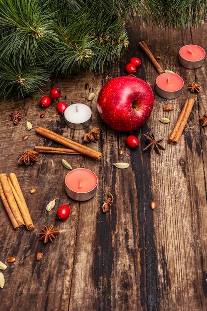 Espíritu árbol de navidad, manzana fresca, canela, velas, cardamomo, anís estrellado. decoraciones de la naturaleza, tableros de madera vintage Foto Premium