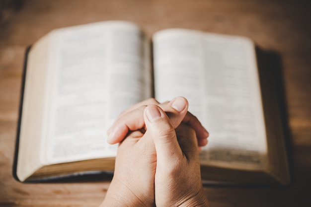 Espiritualidad y religión, las manos juntas en oración en una santa biblia en el concepto de iglesia para la fe. Foto gratis