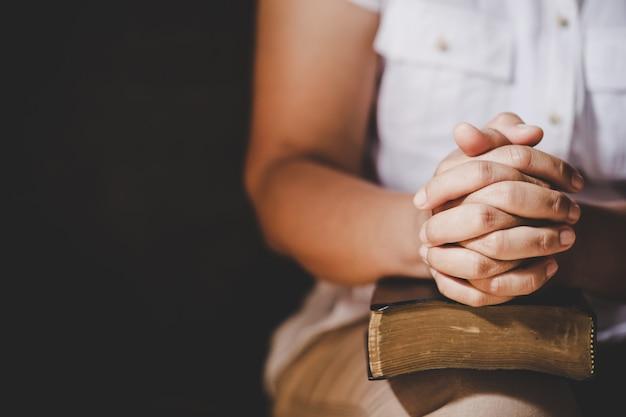 Espiritualidad y religión, las manos juntas en oración sobre una santa biblia en el concepto de iglesia para la fe. Foto gratis