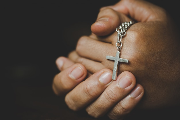 Espiritualidad y religión, mujeres en conceptos religiosos manos rezando a dios mientras sostiene el símbolo de la cruz. nun atrapó la cruz en su mano. Foto gratis