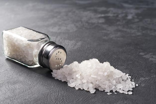 Espolvorea coctelera de sal en la piedra negra, foco selectivo. Foto Premium