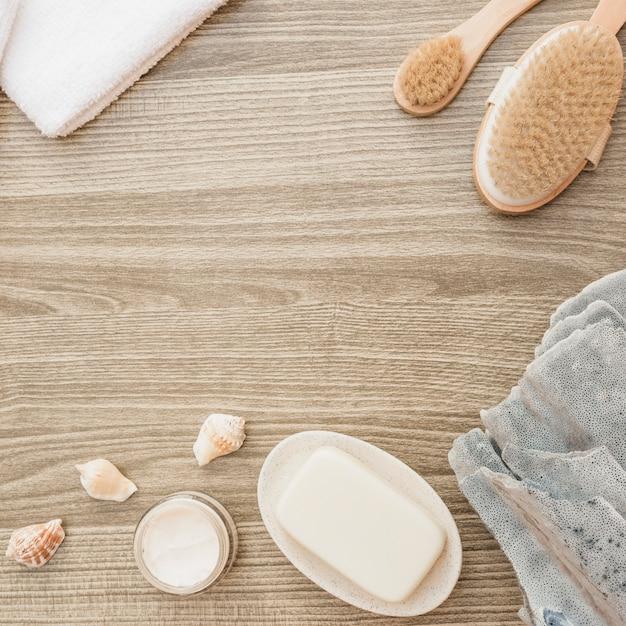 Esponja; concha; jabón; cepillo; toalla y crema hidratante sobre superficie de madera. Foto gratis