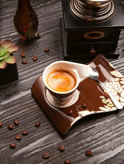 Espuma lechosa cappuchino, latte en taza decorativa y plato marrón con cuchara metálica. Foto gratis