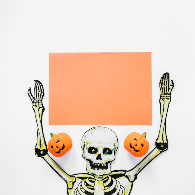 Esqueleto hecho a mano con trozo de papel y calabazas Foto gratis