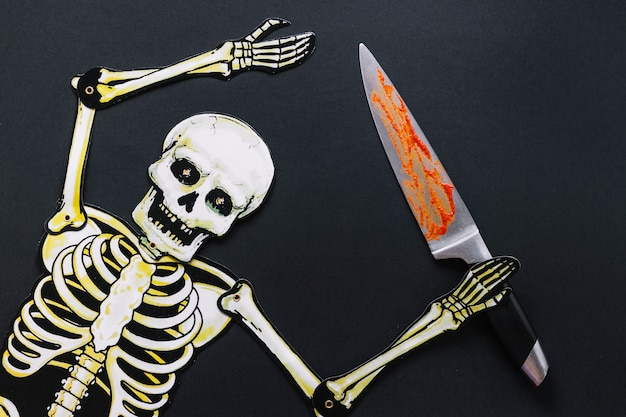 Esqueleto de papel con cuchillo sangriento Foto gratis
