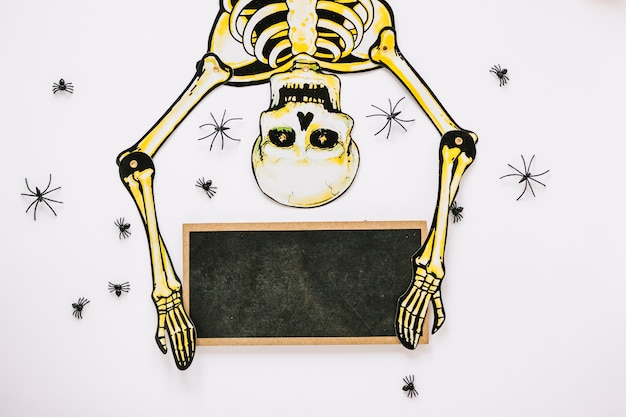 Esqueleto rodeado de arañas con tablero Foto gratis