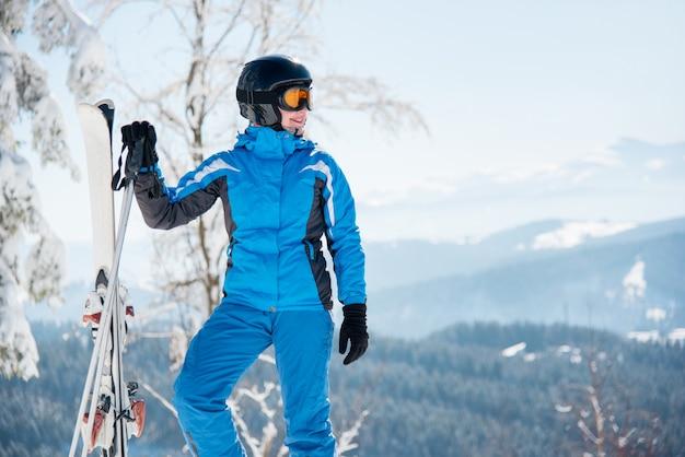 Esquiador femenino con equipo de esquí disfrutando de paisajes impresionantes en las montañas de invierno Foto Premium