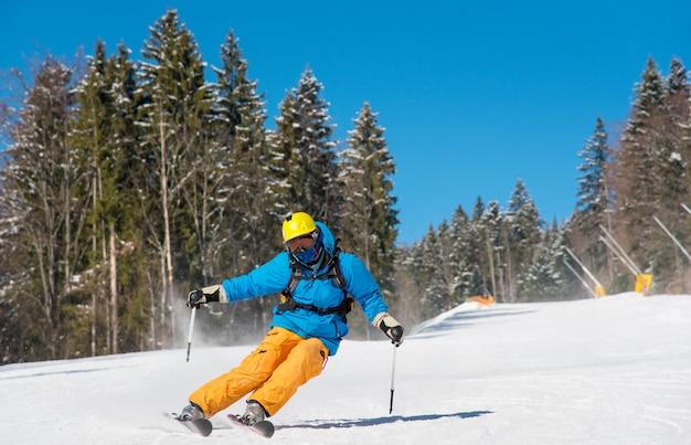 Esquiador montando en las montañas en un día soleado de invierno Foto Premium