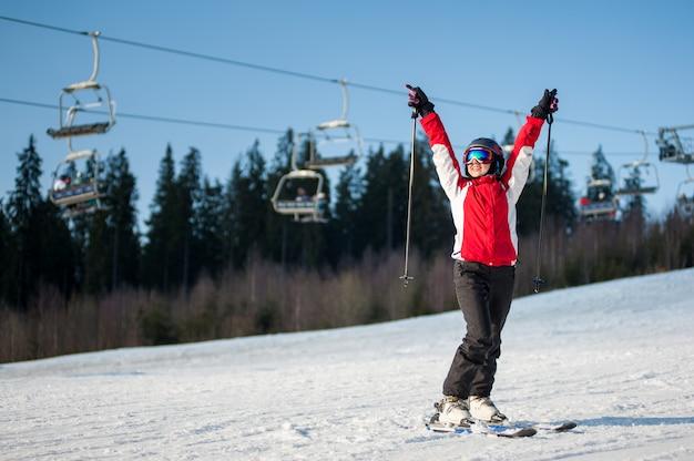 Esquiador de la mujer que se coloca en cuesta nevosa con las manos levantadas en día soleado con el bosque y el cielo azul en fondo. Foto Premium