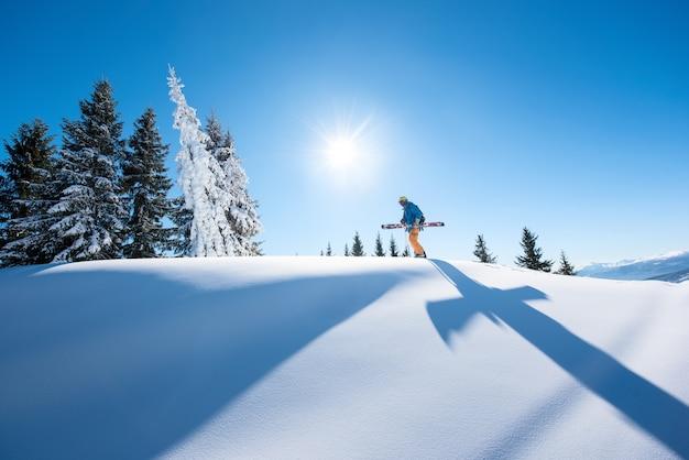 Esquiador en pendiente en las montañas en día de invierno Foto Premium