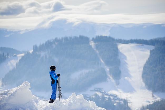 Esquiador de pie en la cima de la montaña y disfrutando de la vista de las hermosas montañas de invierno en un día soleado Foto Premium