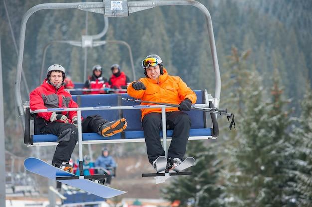 Esquiador y snowboarder montando en remonte Foto Premium