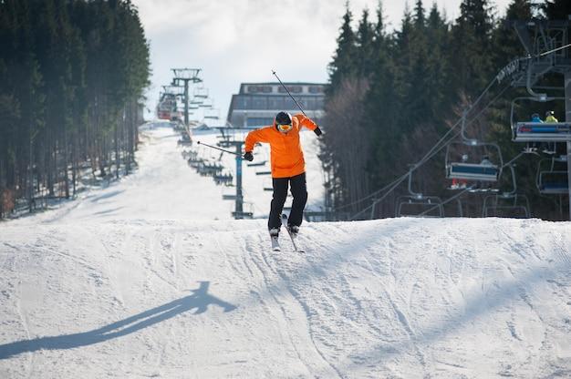 Esquiador volador al saltar desde la ladera de las montañas con una chaqueta naranja realizando un salto alto. Foto Premium