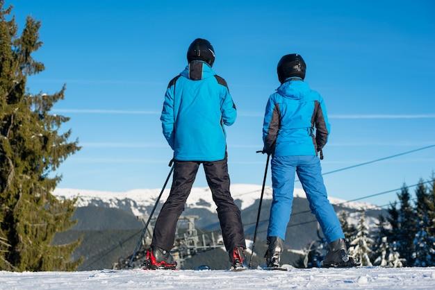 Esquiadores de hombre y mujer de pie juntos en la cima de la montaña disfrutando del hermoso paisaje de montaña en un resort de invierno en un día soleado Foto Premium