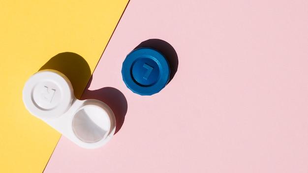 Establecer lentes de contacto sobre fondo naranja y rosa Foto gratis