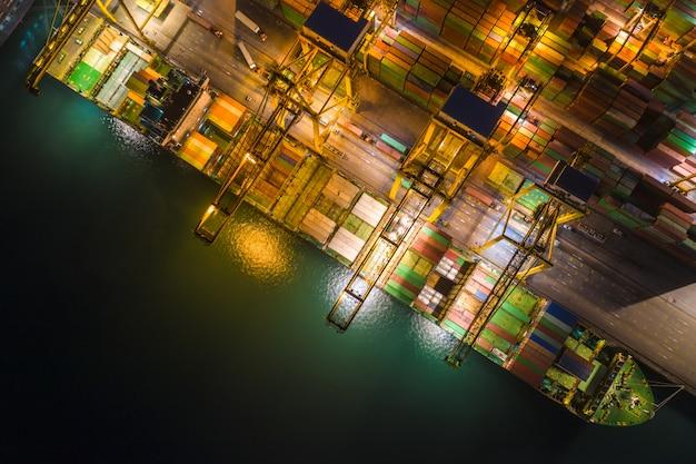 La estación internacional de carga marítima en grandes contenedores de carga se envía por encima de la vista desde la cámara del avión no tripulado en la noche Foto Premium