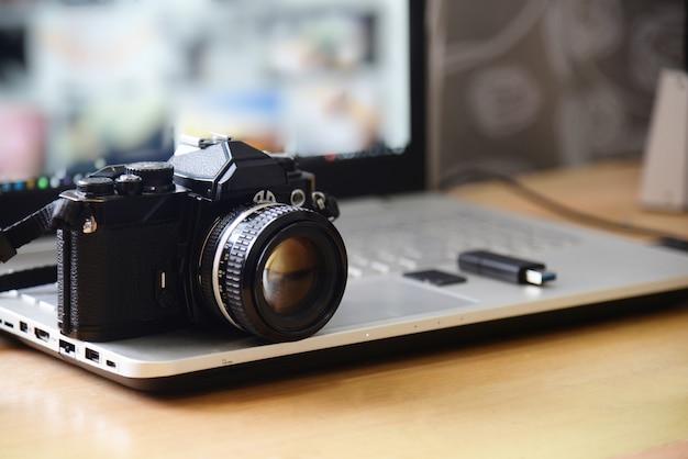 Estación de trabajo de fotografía de estudio digital. cámara dslr de película retro, pantalla de computadora portátil y tarjeta de memoria flash drive Foto Premium