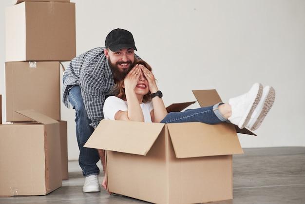 Estado de ánimo juguetón. pareja feliz juntos en su nueva casa. concepción de mudanza Foto gratis