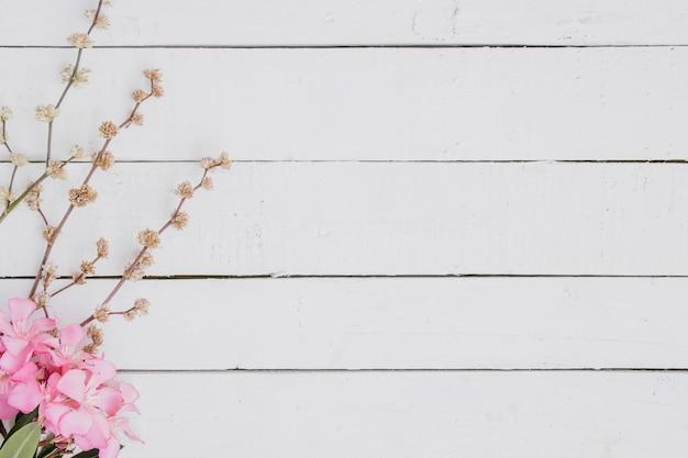 Estampado de flores de ramas de color rosa claro sobre fondo de madera. Foto gratis