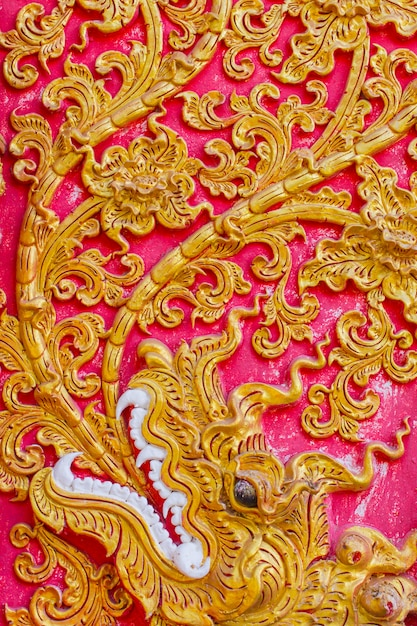 El estampado de plores tailandés grabó en relieve la pintura del cemento con oro y el fondo del color rojo en templo. Foto Premium