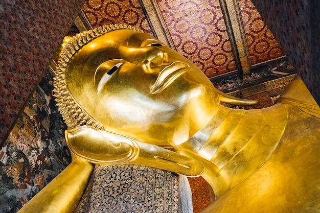 Estatua de buda de oro de gran sueño en el templo en bangkok, tailandia Foto gratis