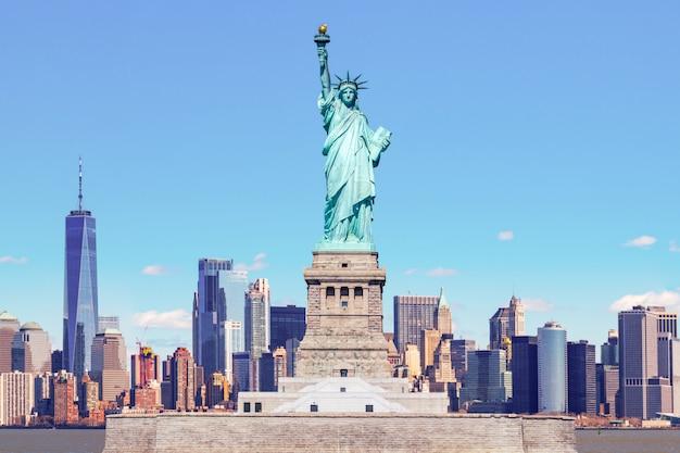 La estatua de la libertad con el one world trade building center sobre el río hudson y el fondo del paisaje urbano de nueva york, monumentos de lower manhattan, nueva york. Foto Premium