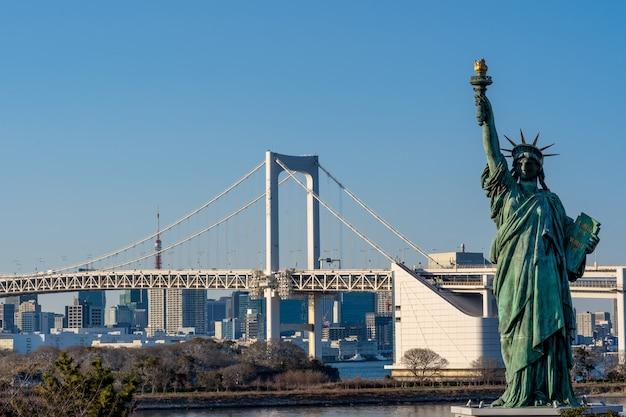 Estatua de la libertad y el puente del arco iris, ubicado en odaiba tokio, japón Foto Premium