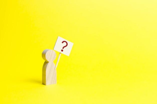 Estatuilla humana de madera con un signo de interrogación. Foto Premium