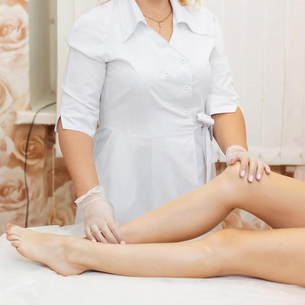 Esteticista junto a las piernas lisas de las clientas después del tratamiento de depilación Foto Premium