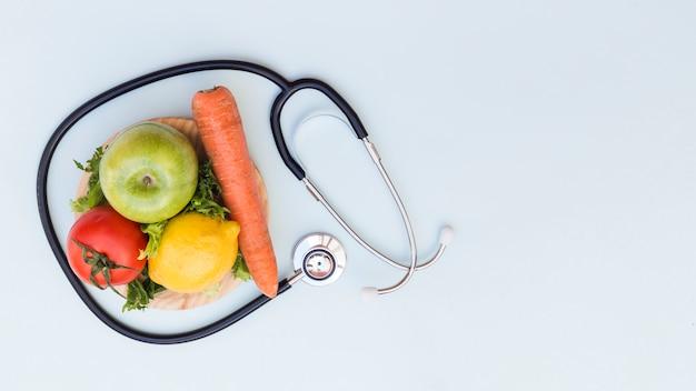 Estetoscopio alrededor de las verduras y frutas frescas sobre fondo blanco Foto gratis