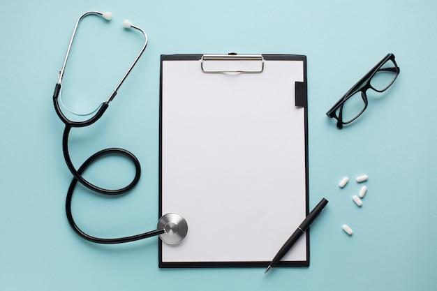 Estetoscopio y bolígrafo en el portapapeles cerca de píldoras con gafas sobre superficie azul Foto gratis