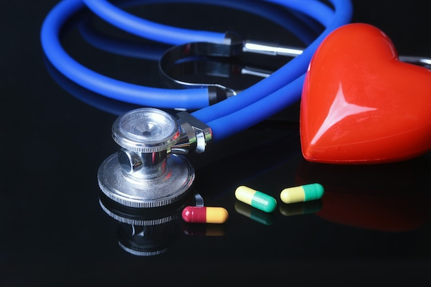 Estetoscopio, corazón rojo y pils surtidos. Foto Premium