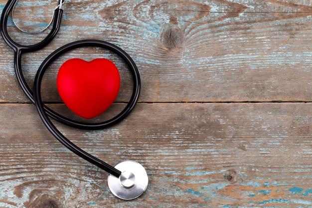 Estetoscopio con corazón rojo sobre una madera con espacio de copia Foto Premium
