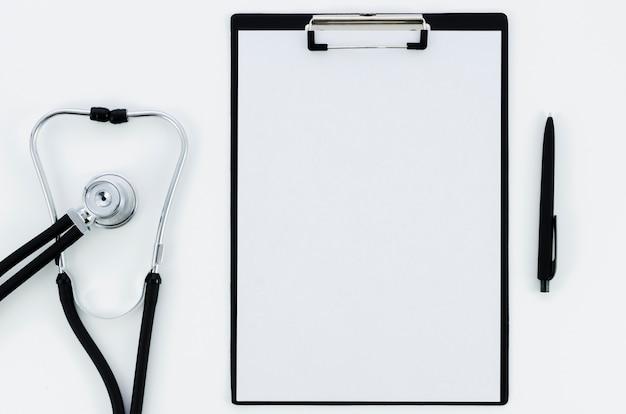 Estetoscopio; libro blanco en el portapapeles con pluma aislada sobre fondo blanco Foto gratis