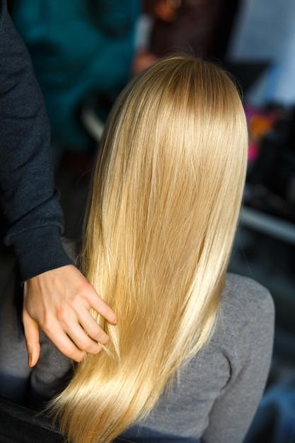 Estilista demostrar cabello rubio femenino Foto Premium