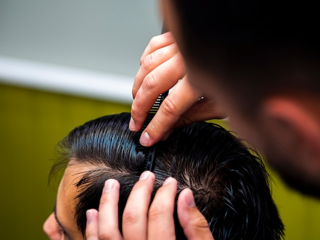 Estilista peinando el cabello del cliente Foto gratis