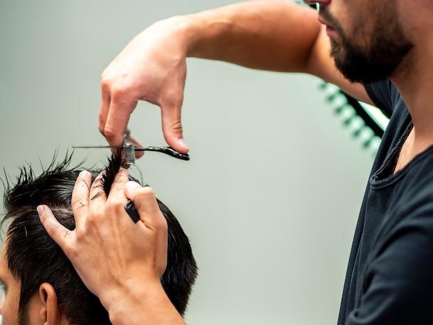 Estilista que corta el cabello del cliente ayudado por tijeras Foto gratis