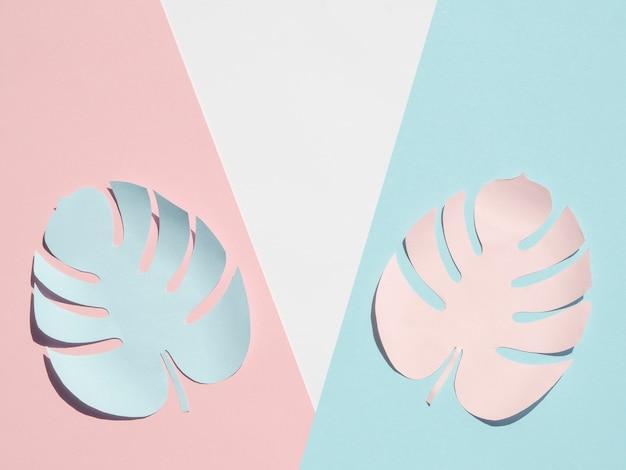 Estilo de corte de papel de hojas de monstera con tonos rosados y azules Foto gratis