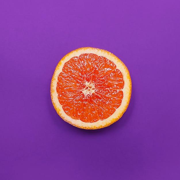 Estilo minimalista, diseño creativo de naranja y pomelo sobre fondo morado Foto Premium
