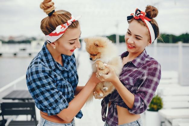 Con estilo pin up chicas con el perrito Foto gratis