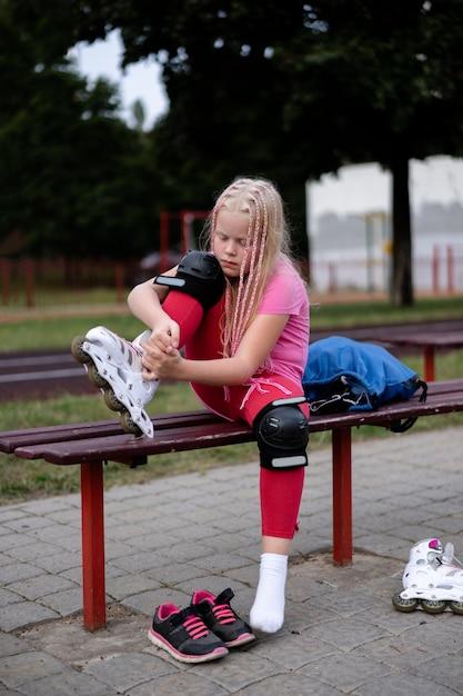Estilo de vida activo en una ciudad moderna, la niña se pone patines en el estadio Foto Premium