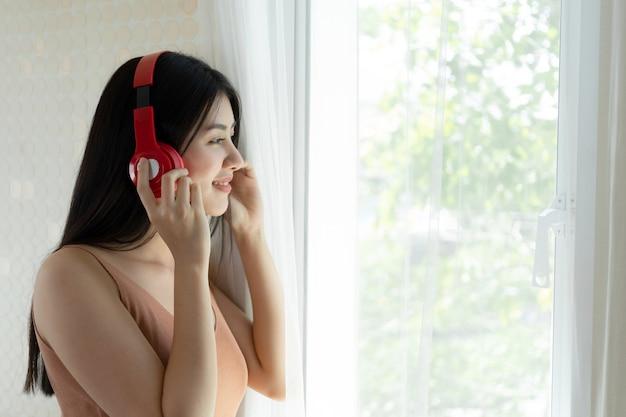 Estilo de vida hermosa mujer asiática linda niña sentirse feliz disfrutar escuchando música con auriculares auriculares en el dormitorio blanco Foto gratis