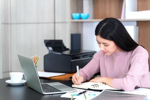 Estilo de vida hermosa mujer de negocios asiática joven usando la computadora portátil en el escritorio de oficina Foto gratis