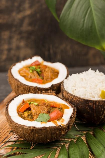 Estofado y arroz en platos de coco alta vista Foto gratis